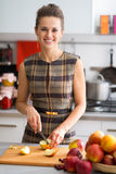 Happy young housewife cutting apple in kitchen Royalty Free Stock Images