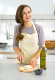 Happy young housewife cutting cheese in kitchen Stock Photo