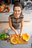 Happy young housewife cutting pumpkin in kitchen Stock Photos