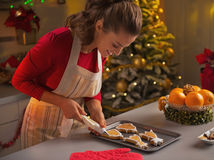 Happy young housewife decorating christmas cookies with glaze Royalty Free Stock Photo