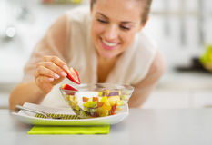 Happy young housewife decorating fruits salad. In kitchen royalty free stock images