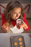 Happy young housewife drinking hot chocolate and eating cookie Stock Image