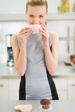 Happy young housewife drinking tea with muffin Royalty Free Stock Photos