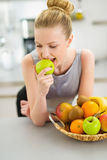 Happy young housewife eating apple in kitchen Royalty Free Stock Photo
