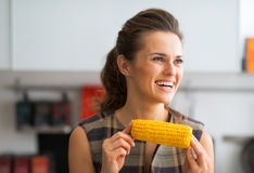 Happy young housewife eating boiled corn Royalty Free Stock Photos