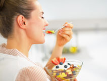 Happy young housewife eating fresh fruit salad in kitchen Royalty Free Stock Photography