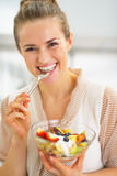 Happy young housewife eating fresh fruit salad Stock Image