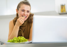 Happy young housewife eating grape and using laptop in kitchen Royalty Free Stock Image