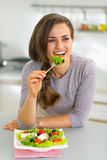 Happy young housewife eating greek salad Royalty Free Stock Photo