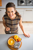 Happy young housewife eating pumpkin soup Stock Photos