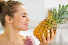 Happy young housewife enjoying fresh pineapple Royalty Free Stock Photography
