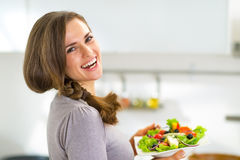 Happy young housewife with greek salad Royalty Free Stock Photos