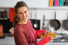 Happy young housewife holding baked pumpkin Stock Image