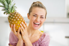 Happy young housewife holding fresh pineapple Royalty Free Stock Photo