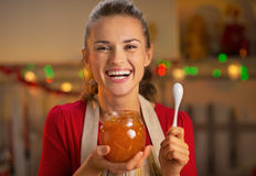 Happy young housewife holding orange jam Stock Photos