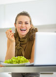Happy young housewife with laptop eating grape in kitchen Royalty Free Stock Photos
