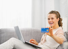 Happy young housewife with laptop showing credit card Stock Photography
