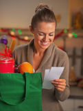 Happy young housewife looking on checks after christmas shopping Royalty Free Stock Images