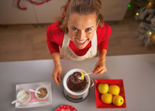 Happy young housewife making apple in chocolate glaze in kitchen Royalty Free Stock Photos