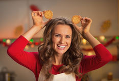 Happy young housewife making ears using christmas cookies Stock Photo