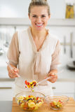 Happy young housewife making fruits salad Royalty Free Stock Photography