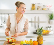 Happy young housewife making fruits salad. In modern kitchen royalty free stock photos