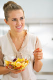Happy young housewife mixing fruit salad Royalty Free Stock Image