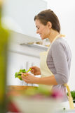 Happy young housewife mixing salad in modern kitch Royalty Free Stock Images