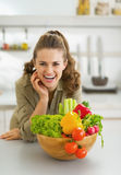 Happy young housewife near plate full of vegetables Royalty Free Stock Photo