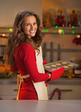 Happy young housewife with pan of christmas cookies Stock Image