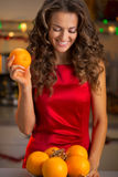 Happy young housewife with plate of oranges Stock Photo