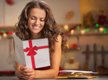Happy young housewife reading christmas postcard in kitchen Stock Photos