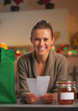 Happy young housewife with receipts from christmas purchases. Happy young housewife  in kitchen with receipts from christmas purchases Royalty Free Stock Photo