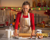 Happy young housewife rolling pin doughin kitchen Royalty Free Stock Images