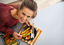 Happy young housewife serving baked pumpkin Stock Photo