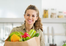 Happy young housewife with shopping bag full of vegetables royalty free stock images