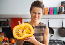 Happy young housewife showing half of pumpkin Stock Photos