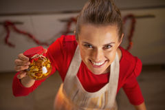 Happy young housewife showing jar with honey nuts Stock Photography