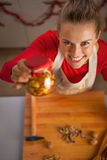Happy young housewife showing jar with honey nuts Royalty Free Stock Photo