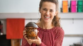 Happy housewife showing jar of pickled mushrooms Royalty Free Stock Photos