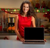 Happy young housewife showing laptop blank screen in christmas d Stock Image