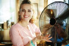 Happy young housewife showing metallic floor standing fan royalty free stock photography