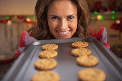 Happy young housewife showing pan with christmas cookies Royalty Free Stock Images