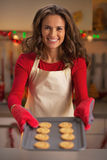 Happy young housewife showing pan with christmas cookies Stock Photography