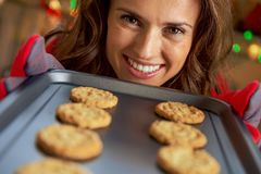 Young housewife showing pan with christmas cookies stock image