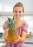 Happy young housewife showing pineapple Royalty Free Stock Photography