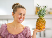 Happy young housewife showing pineapple Royalty Free Stock Image