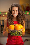 Happy young housewife showing plate of oranges Royalty Free Stock Image