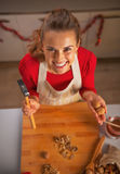 Happy young housewife showing walnuts and hammer Stock Photo