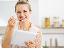 Happy young housewife with tablet pc eating fruits salad Royalty Free Stock Photo
